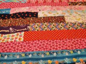 For the quilted side, I used the jelly-roll strip method without using strips from a jelly roll. Instead, I used my longest pieces of fabric from my scrap stash and cut them all to be 6 inches high – I didn't tinker with the length. The fast and easy method is simply sewing the end strips together. Once that was completed, I had one very long strip of fabric.