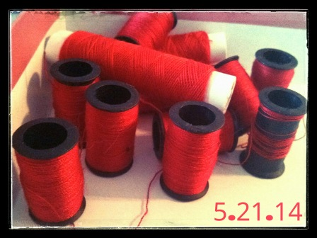 SPOOLS OF RED THREAD FROM MY SEWING STASH.